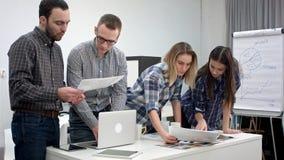 2 архитектора обсуждая план пока женские сотрудники смотря цветовую палитру Стоковые Фото