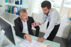 2 архитектора обсуждая светокопии в офисе Стоковая Фотография RF