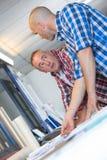 2 архитектора обсуждая светокопию деталей Стоковое Изображение