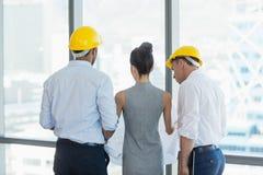 3 архитектора обсуждая над светокопией в офисе Стоковые Изображения