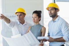 3 архитектора обсуждая над светокопией Стоковые Изображения