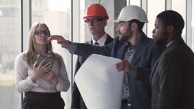 4 архитектора обсуждая план здания сток-видео