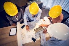 4 архитектора обсуждая светокопии в встрече Стоковая Фотография RF