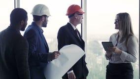 4 архитектора обсуждая строящ план видеоматериал