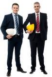 2 архитектора представляя с шлемом безопасности Стоковые Изображения