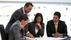 4 архитектора смотря планы на таблице видеоматериал