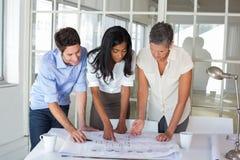 3 архитектора смотря светокопии Стоковая Фотография