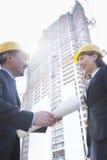 2 архитектора усмехаясь на строительной площадке держа светокопию Стоковые Изображения