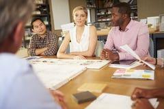 6 архитекторов сидя вокруг таблицы имея встречу Стоковые Изображения