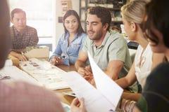 6 архитекторов сидя вокруг таблицы имея встречу Стоковая Фотография