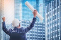 Архитекторы держат бумажные светокопии для того чтобы поднять их руки для того чтобы показать th стоковая фотография rf