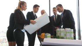 Архитекторы и инвесторы смотря модель домов видеоматериал