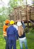 Архитекторы обсуждая над неполной деревянной кабиной Стоковые Изображения