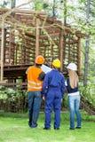 Архитекторы обсуждая над неполной кабиной тимберса Стоковая Фотография RF
