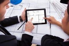 Архитекторы при цифровая таблетка работая на светокопии стоковые фото
