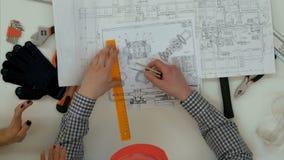 Архитекторы проверяя светокопии с разметочным циркулем и правителем видеоматериал