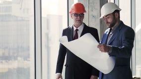 Архитекторы разговаривая с планом здания в руках акции видеоматериалы