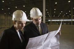 Архитекторы смотря светокопию в складе Стоковое Изображение