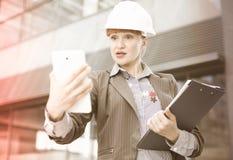 Архитектор взрослой женщины в шлеме при печатные документы работая ith Стоковая Фотография
