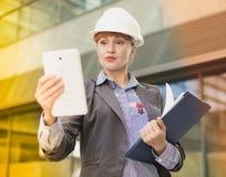 Архитектор взрослой женщины в шлеме при печатные документы работая ith Стоковое Фото