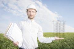Архитектор в белом шлеме держит чертеж конструкции многоквартирного дома на его ладони Стоковая Фотография RF