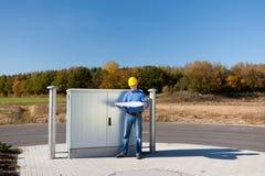 Архитектор держа светокопию пока стоящ против электрической коробки Стоковая Фотография RF