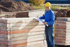 Архитектор держа светокопию стогом деревянных планок на месте Стоковое фото RF