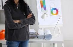 Архитектор женщины стоя с пересеченными оружиями в офисе Стоковое фото RF