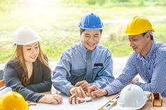 Архитектор 2 женщин человека одной рисует план, на большом листе бумаги на столе офиса и доме строений модельном от деревянных ба Стоковое Изображение RF