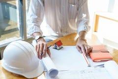 Архитектор или инженер работая на светокопии на рабочем месте на деревянном столе - архитектурноакустический проект, концепция ко стоковые изображения