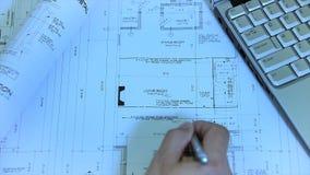 Архитектор или инженер работая на светокопии на рабочем месте архитекторов - архитектурноакустическом проекте акции видеоматериалы