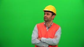 Архитектор или рабочий-строитель смотря вверх на зеленом экране Правильная позиция сток-видео