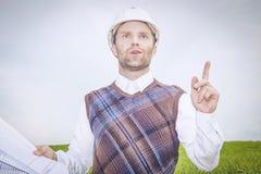 Архитектор инженера в белых шлеме и чертежах думает, анализирует, приходит вверх с хорошими идеей или решением к комплексной проб Стоковая Фотография RF