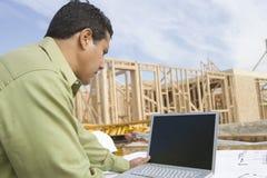 Архитектор используя компьтер-книжку на месте стоковая фотография rf