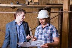 Архитектор и мастер проверяя планы здания Стоковое Изображение