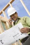 Архитектор на звонке с светокопией в руке Стоковая Фотография