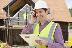 Архитектор на строительной площадке используя мобильный телефон стоковые фото