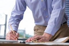 Архитектор работая на плане строительства на офисе inspe инженера Стоковое Изображение RF