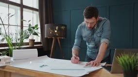 Архитектор работая на светокопии с spesial инструментами и карандашем, концом вверх Мужской архитектор на работе, только руках с  акции видеоматериалы