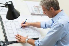 Архитектор работая на чертежном столе