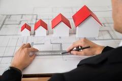 Архитектор с различными моделями дома размера на светокопии Стоковое Фото