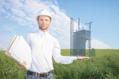 Архитектор с чертежами в белом шлеме держит в схеме размещения руки конструкции multi многоквартирного дома Стоковая Фотография