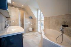 Архитектурноакустически построил bathroom с роскошный крыть черепицей, белые шторками, ванной и просторным дождем стоковая фотография