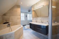 Архитектурноакустически построил bathroom с роскошный крыть черепицей, белые шторками, ванной и просторным дождем стоковое фото rf