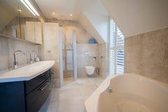 Архитектурноакустически построил bathroom с роскошный крыть черепицей, белые шторками, ванной и просторным дождем стоковое изображение rf