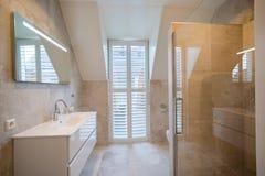 Архитектурноакустически построил bathroom с роскошный крыть черепицей, белые шторками, ванной и просторным дождем стоковое изображение