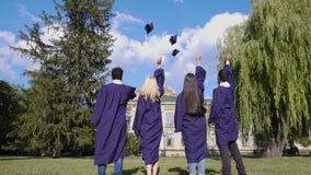 Аспиранты бросая квадратные шляпы вверх, популярная традиция, высшее образование сток-видео