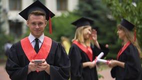 Аспиранты стоя в парке, молодом человеке при smartphone смотря камеру видеоматериал