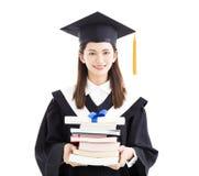 Аспирант держа диплом и книги Стоковое Изображение
