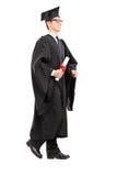 Аспирант идя с дипломом в его руке Стоковое Изображение RF